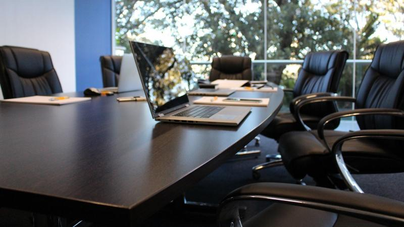 Image of board room and laptop on table